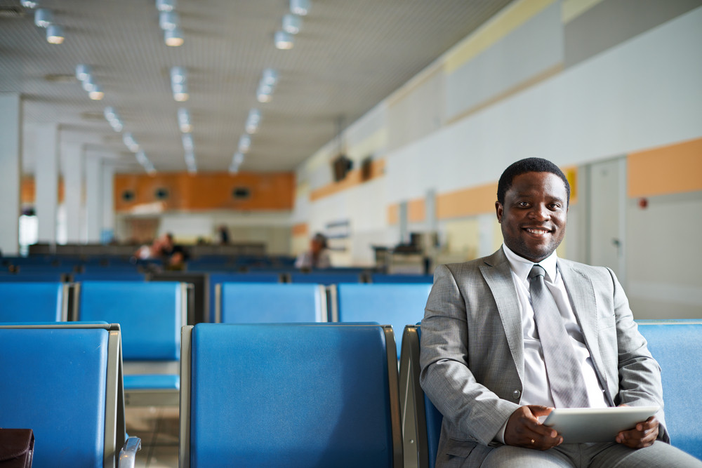 Young African-american Businessman With Touchpad Looking At Camera In Airport