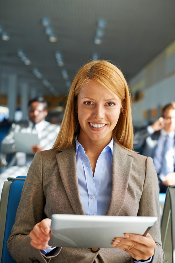 Smiling Young Woman With Touchpad Looking At Camera In Airport With Two Businessmen On Background