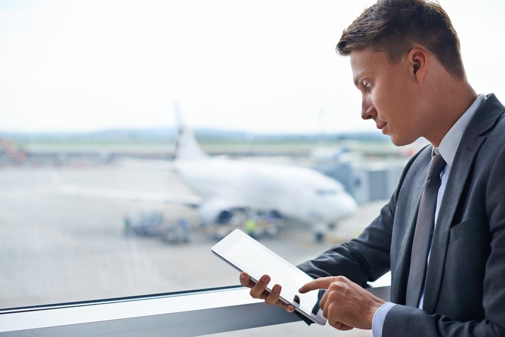 Elegant Businessman Touching Screen Of Digital Tablet In Airport
