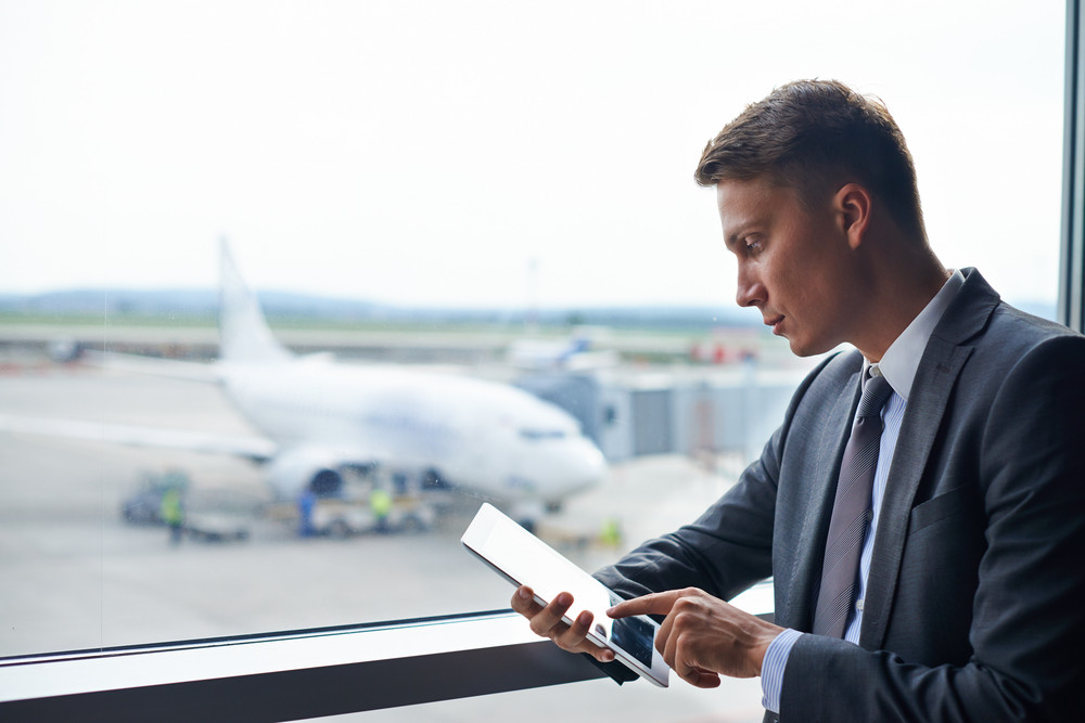 Elegant Businessman Using Touchpad In Airport
