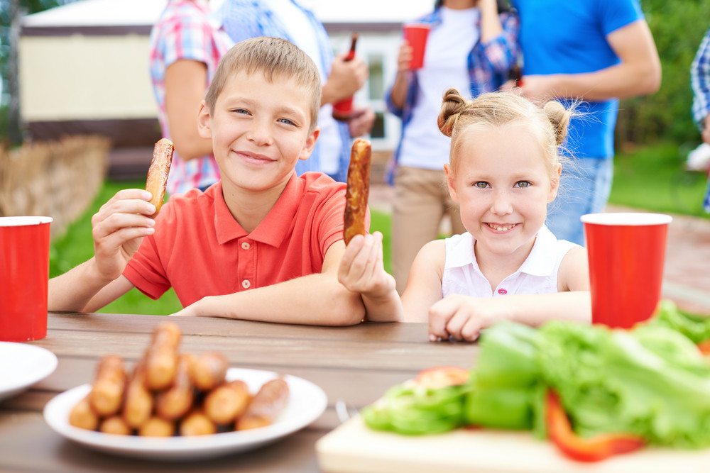 Cute Siblings With Sausages Looking At Camera At Weekend With Their Parents On Background