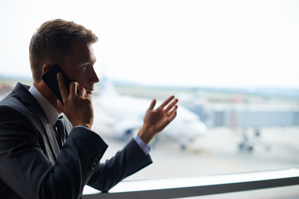 Elegant Businessman Speaking On Cellular Phone In Airport