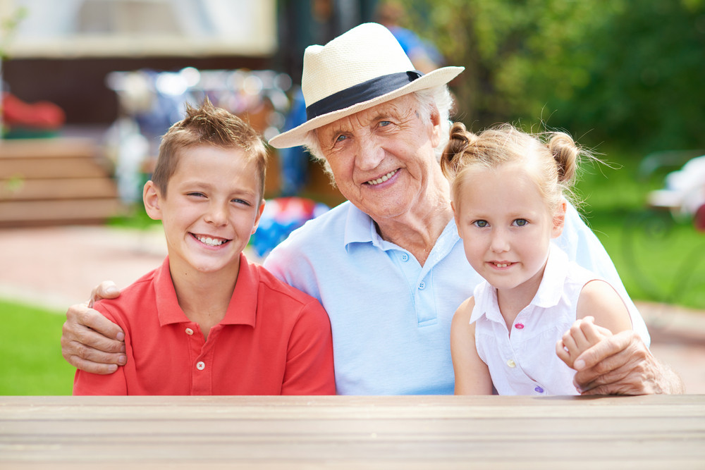 Cute Siblings With Their Grandfather Looking At Camera At Weekend Outdoors
