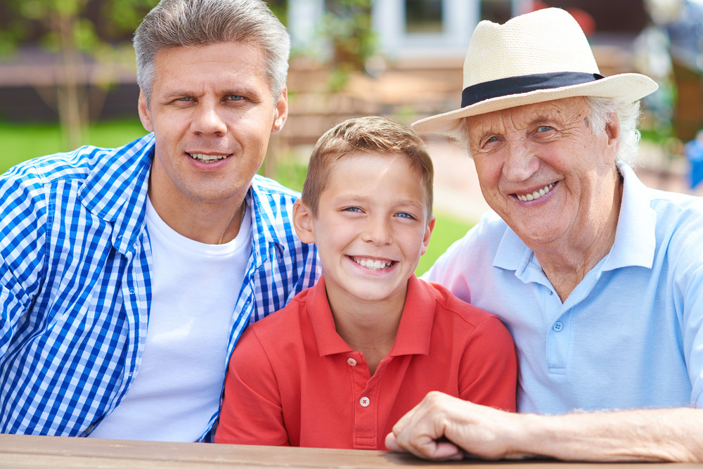 Cute Boy With His Grandfather And Father Looking At Camera At Weekend Outdoors