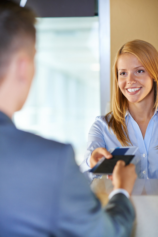 Attractive Young Woman Giving Documents To Businessman At Airport Check-in Counter