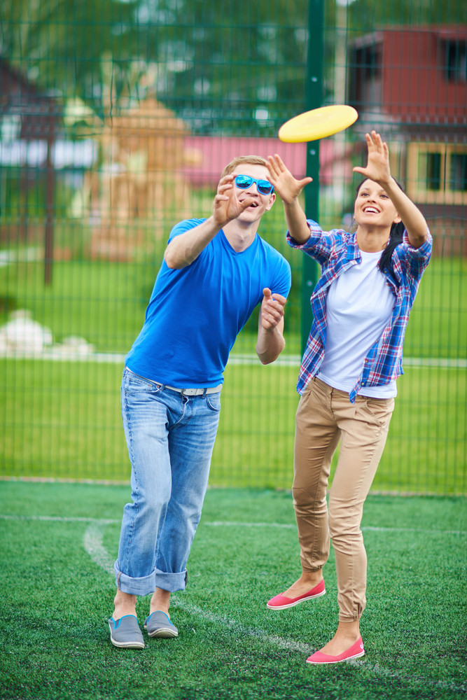 Young Couple Playing With Flying Disc In The Countryside