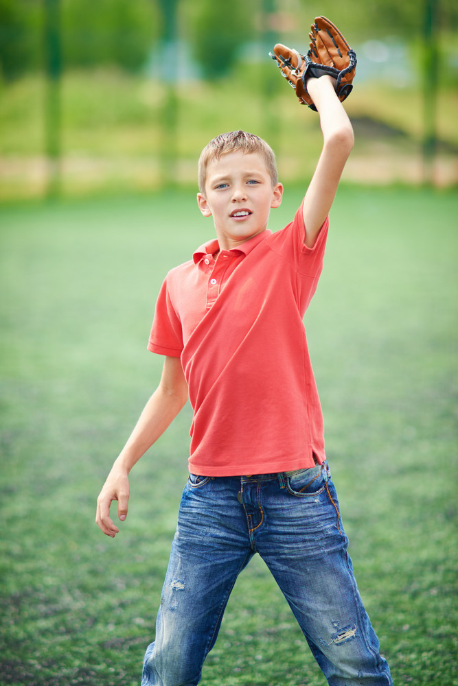 Portrait Of Active Boy Catching Baseball In The Countryside