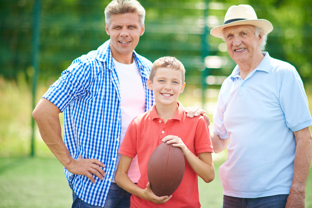 Cute Boy With Rugby Ball And His Grandfather And Father Looking At Camera Outdoors