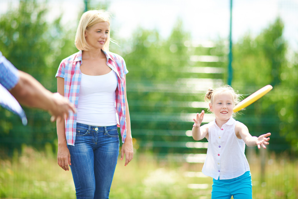 Little Girl Playing With Flying Disc In The Countryside With Her Mother Near By
