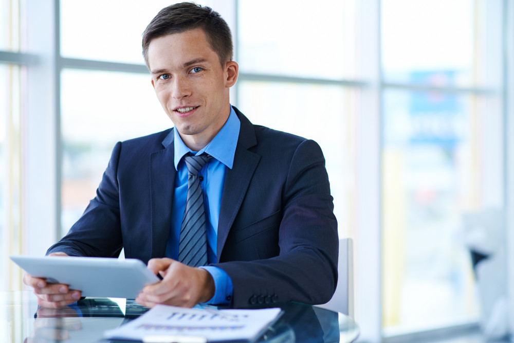 Smiling Businessman With Touchpad Sitting At Workplace In Office