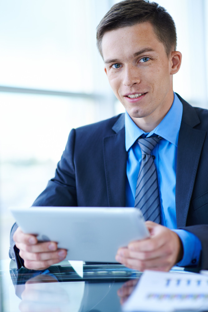 Attractive Businessman With Digital Tablet Looking At Camera In Office