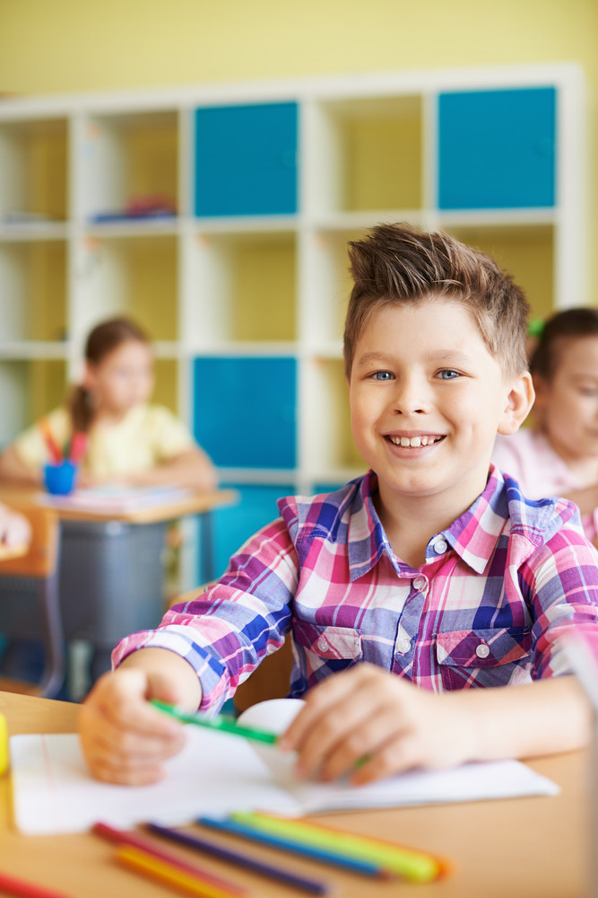 Portrait Of A Cute Schoolboy Looking At Camera On Background Of His Classmates