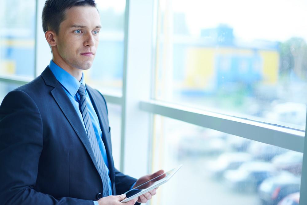 Businessman In Formalwear With Digital Tablet Looking Through Window