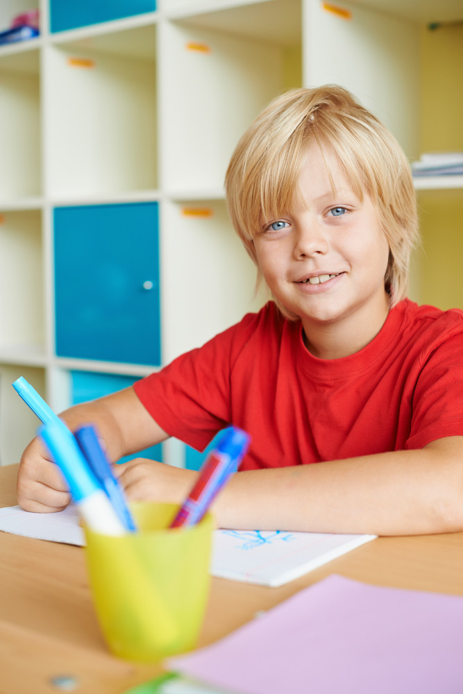 Portrait Of A Cute Schoolboy Looking At Camera While Drawing