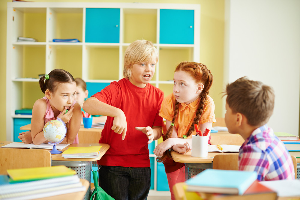 Portrait Of Cute Boy Talking To His Classmates At Workplace