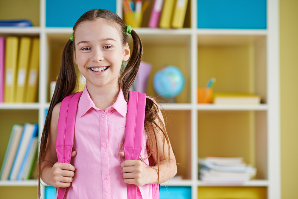 Smiling Schoolgirl With Backpack Looking At Camera