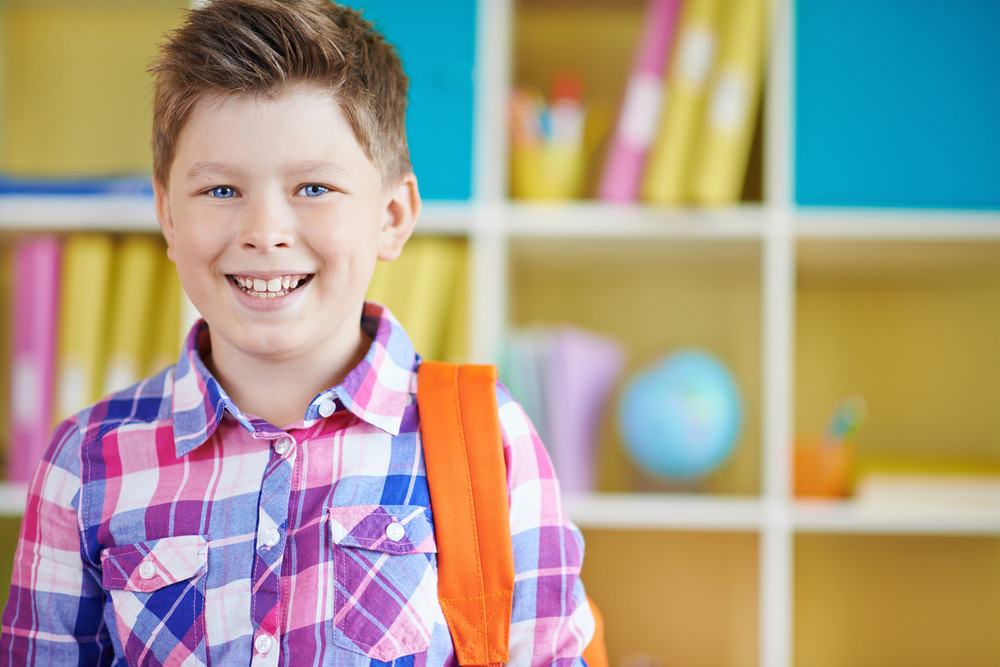 Cheerful Schoolboy With Backpack Looking At Camera