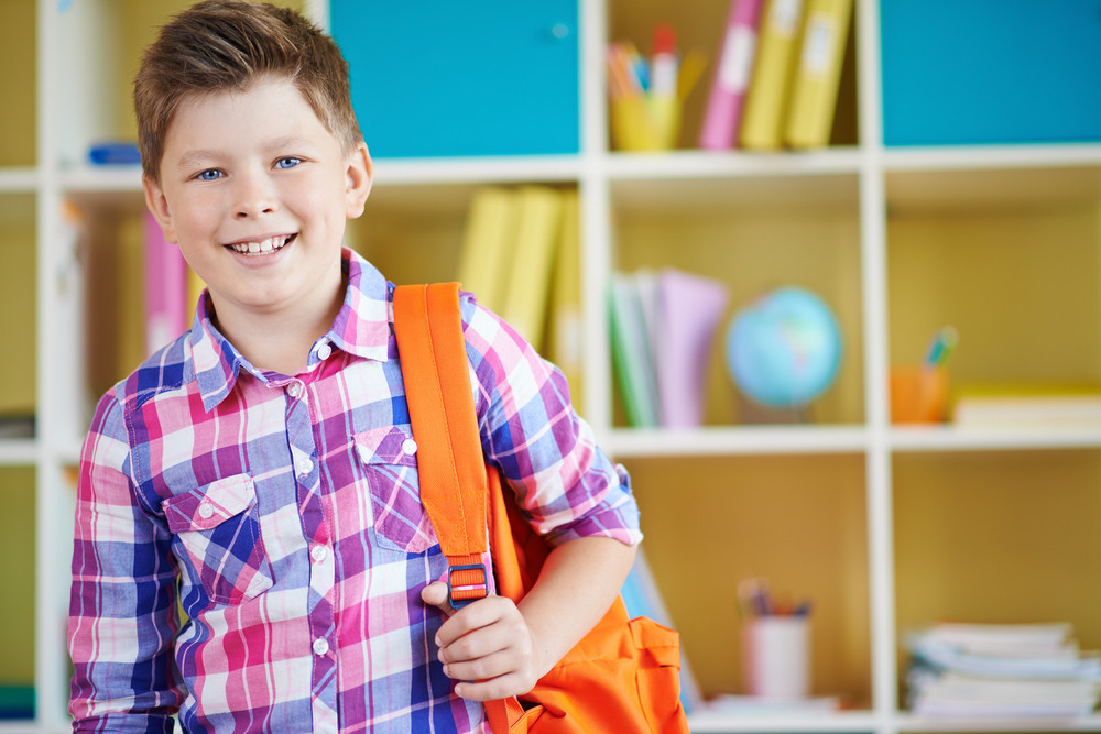 Portrait Of Smiling Schoolboy With Backpack Looking At Camera