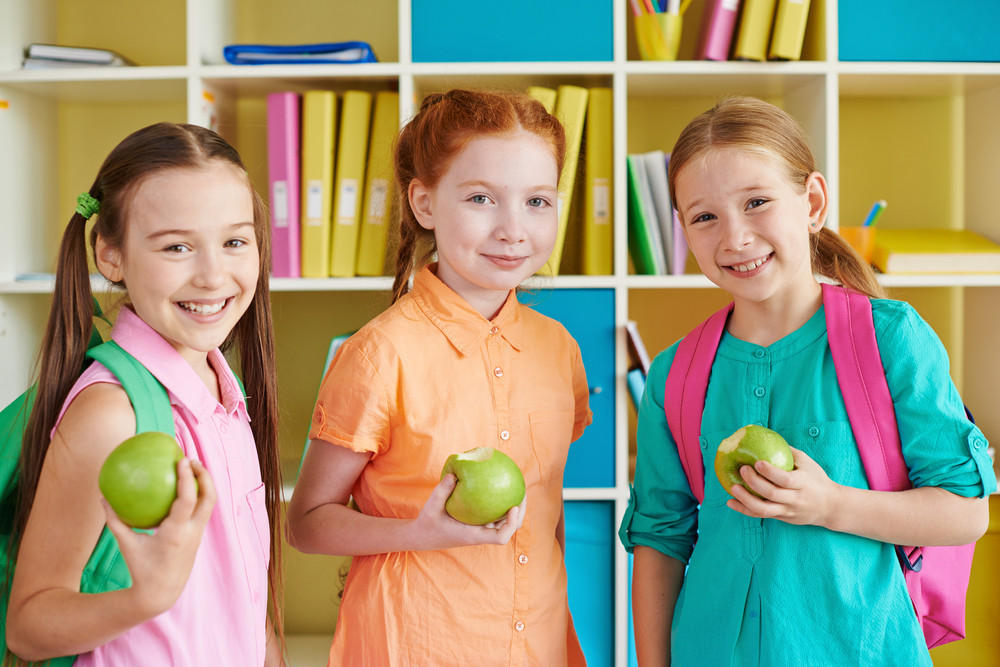 Three Charming Girls With Green Apples Looking At Camera