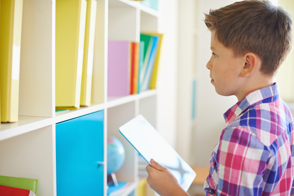 Serious Schoolboy With Touchpad Looking At Books On Shelf