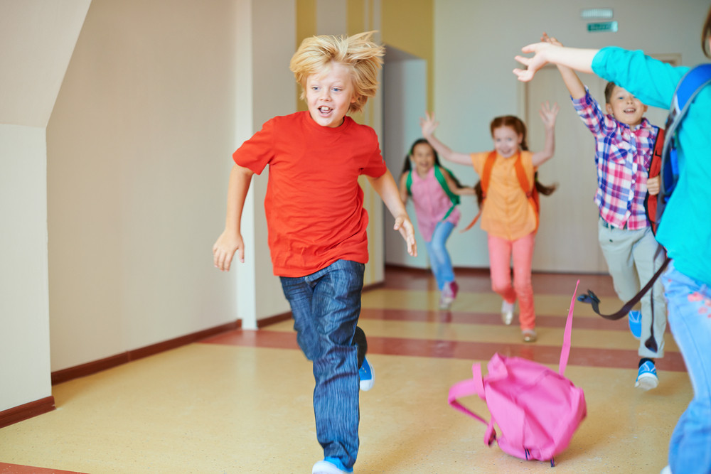 Portrait Of Happy Classmates With Backpacks Running Down The Corridor After Lesson