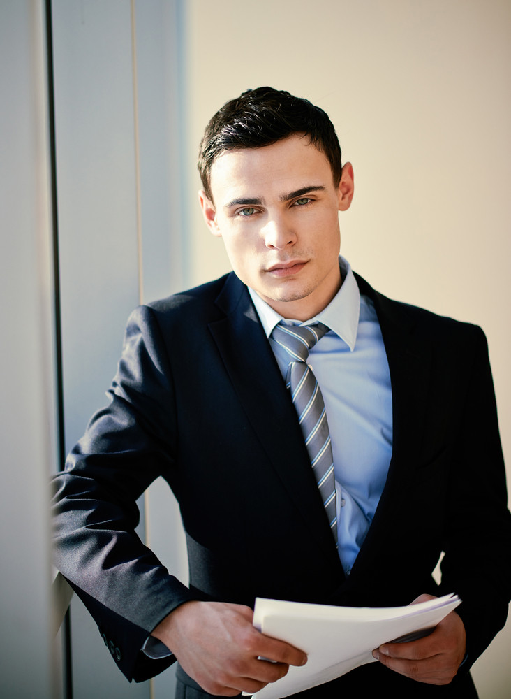 Serious Young Businessman With Papers Looking At Camera