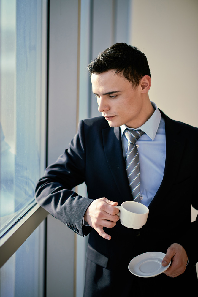 Serious Young Businessman With Cup Looking Through Window