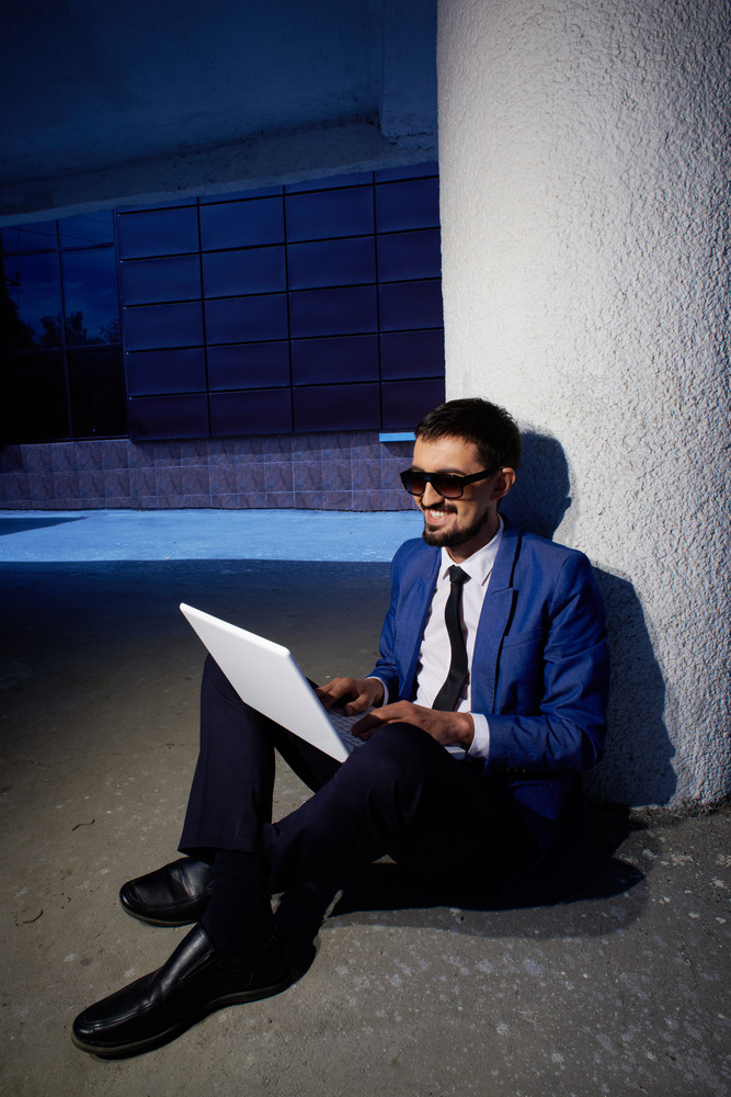 Image Of Successful Businessman In Formalwear Using Laptop Outside