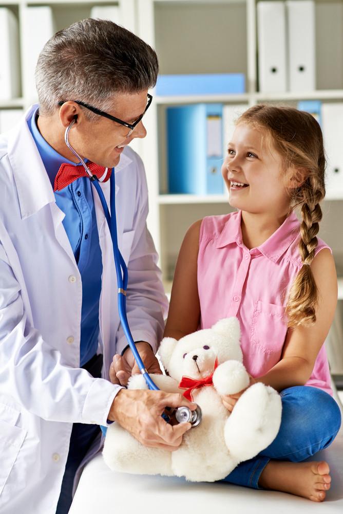Joyful Girl Looking At Her Doctor Examining Teddy Bear In Hospital