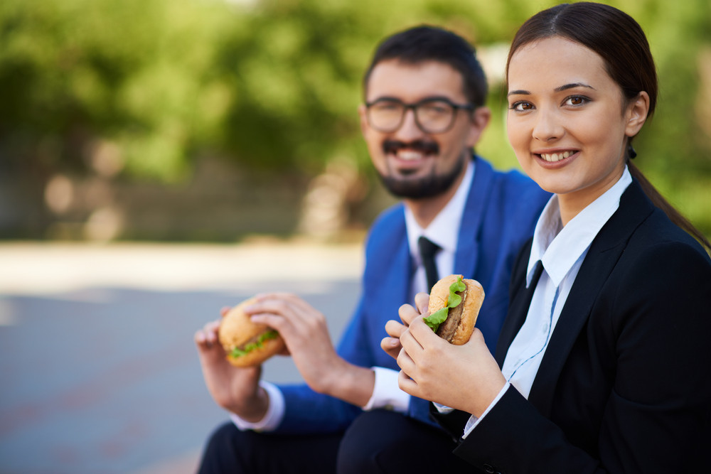 Image Of Pretty Businesswoman With Sandwich Looking At Camera Outside On Background Of Her Co-worker