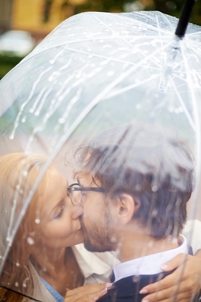 Portrait Of Affectionate Couple Kissing Under Umbrella Outside