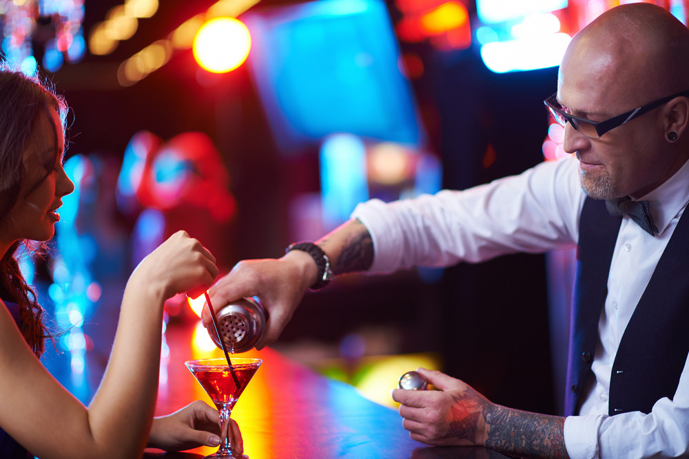 Bald Male In Eyeglasses Pouring Cocktail To A Young Girl In The Bar