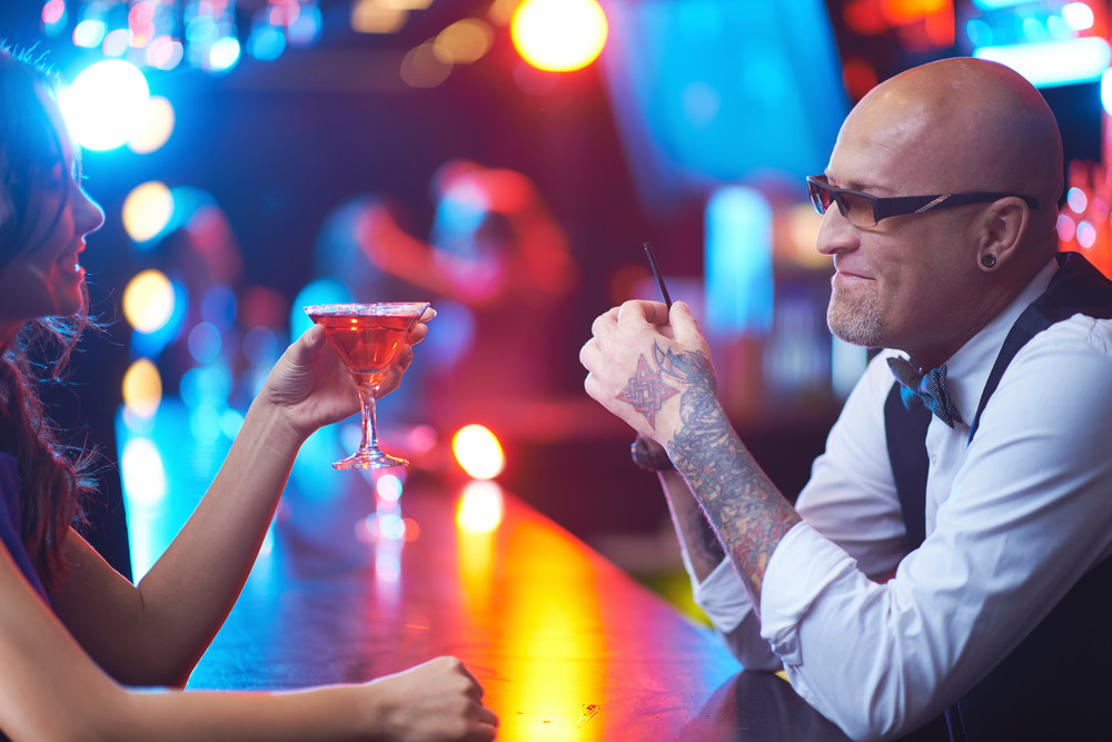 Bald Male In Eyeglasses And Happy Young Girl With Drink Looking At One Another In The Bar
