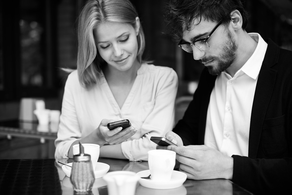 Portrait Of Young Couple Using Their Cellphones In Cafe