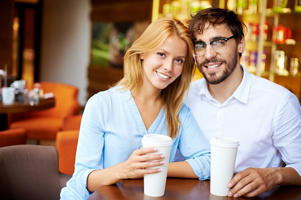 Portrait Of Young Couple Sitting In Cafe