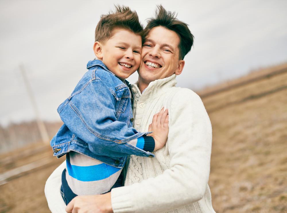 Photo Of Happy Man Embracing His Son And Both Looking At Camera