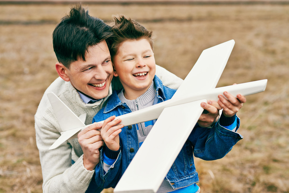 Photo Of Happy Boy With Toy Airplane And His Father Playing Together