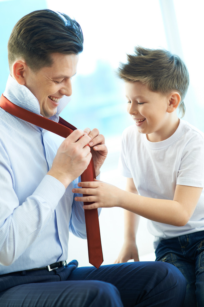 Photo Of Happy Boy Looking At His Father Tying Necktie