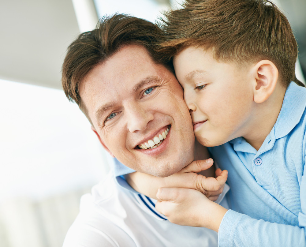Photo Of Happy Man Looking At Camera While His Son Embracing And Kissing Him