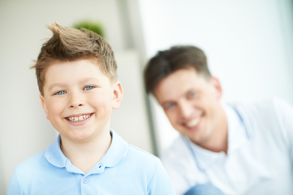 Photo Of Happy Boy Looking At Camera On Background Of His Father