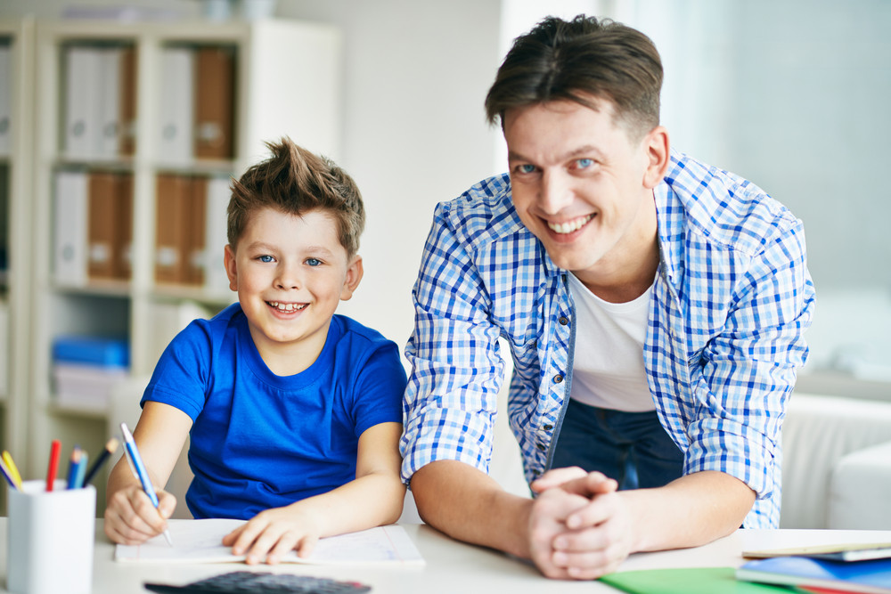 Photo Of Happy Man And His Son Looking At Camera At Home