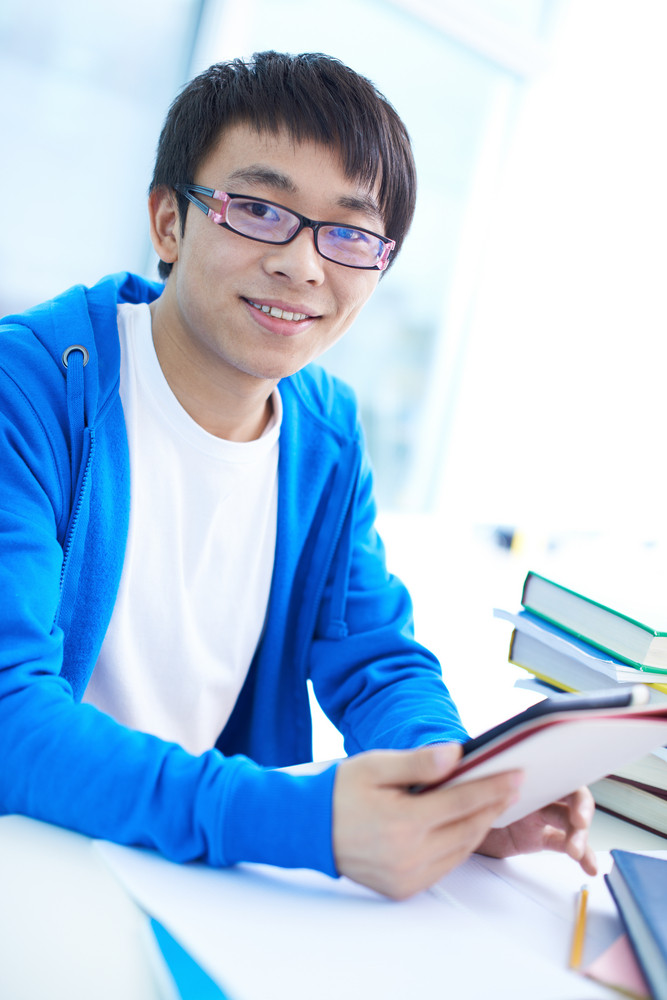 Portrait Of Successful Asian Student In Eyeglasses Looking At Camera