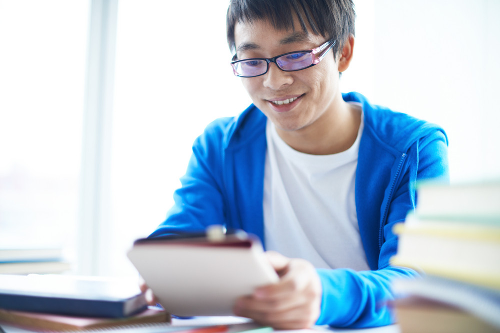 Portrait Of Successful Asian Student In Eyeglasses Working At Lesson
