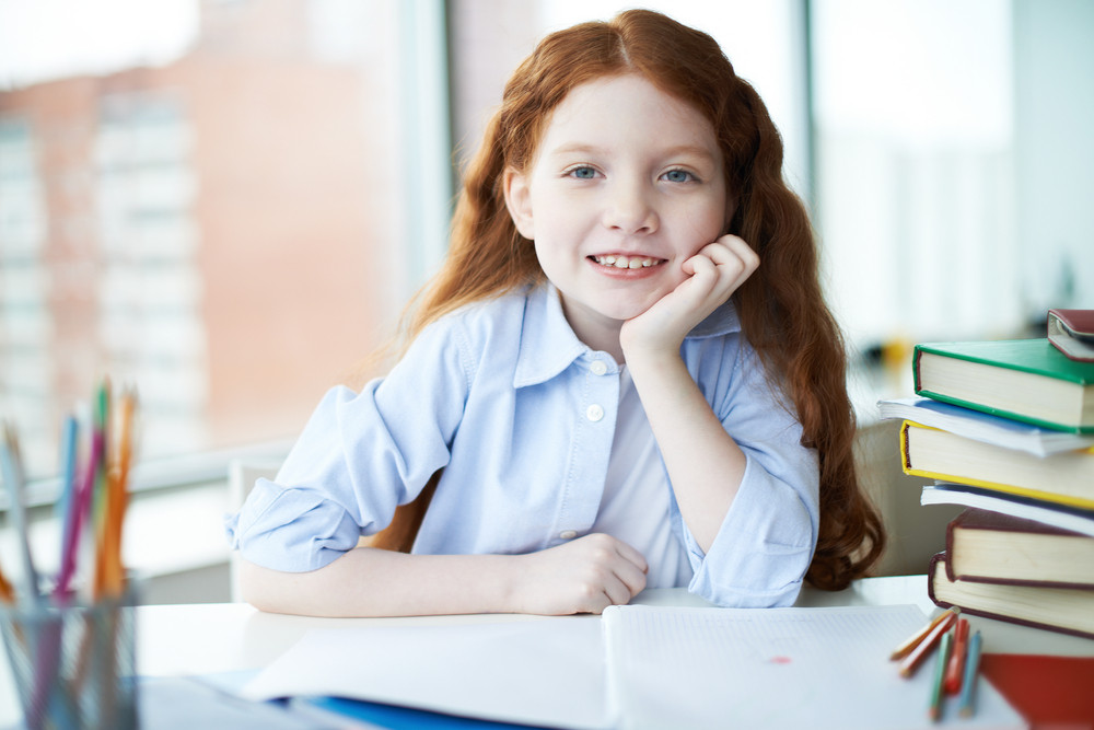 Cute Little Girl Sitting By Table With Crayons And Open Copybook In Front Of Her