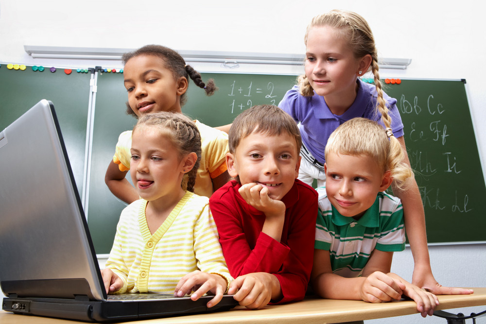 Portrait Of Smart Schoolgirls And Schoolboy Looking At The Laptop With Blackboard On Background