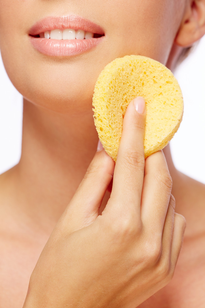 Young Woman Cleaning Her Face With Sponge