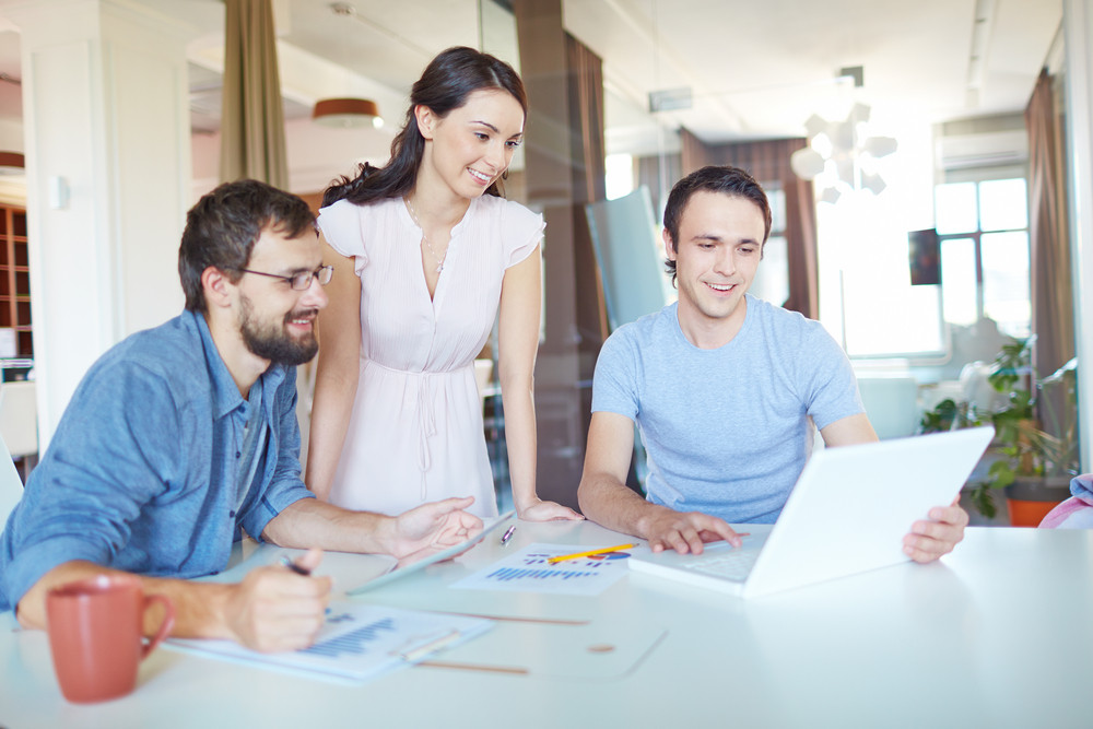 Group Of Three Successful Business Partners In Casual Working At Meeting In Office