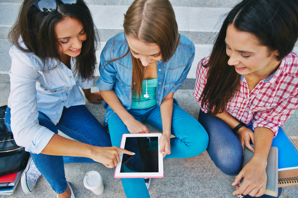 Modern Teen Girls Using Touchpad While Sitting On Stairs