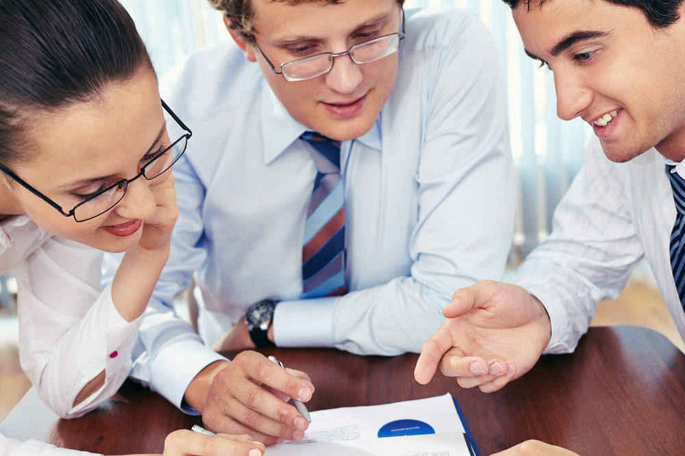 Three Business People Examining Paper
