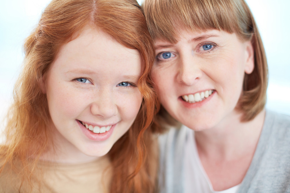 Lovely Girl And Her Mother Looking At Camera With Toothy Smiles